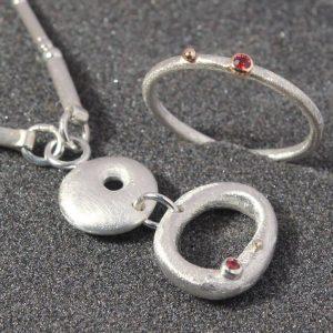 Pakabukas ir žiedas iš sidabro su raudonaisiais safyrais.