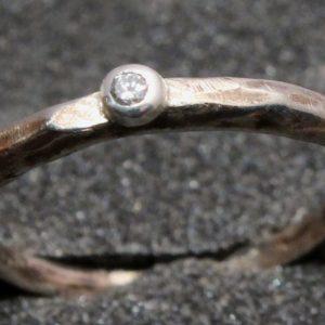 Oksiduotas baltojo aukso žiedas su 0,05 ct deimantu.